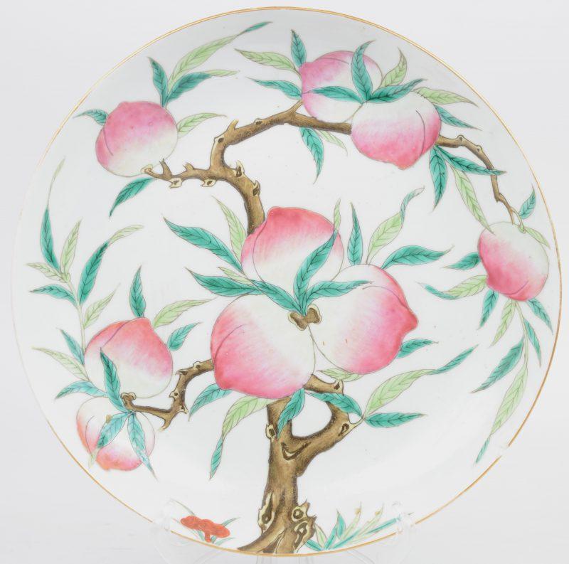 Een bord van Chinees porselein met een decor van negen perziken. Onderaan gemerkt. Kleine randschilfer. Guang XU (1857 - 1907)