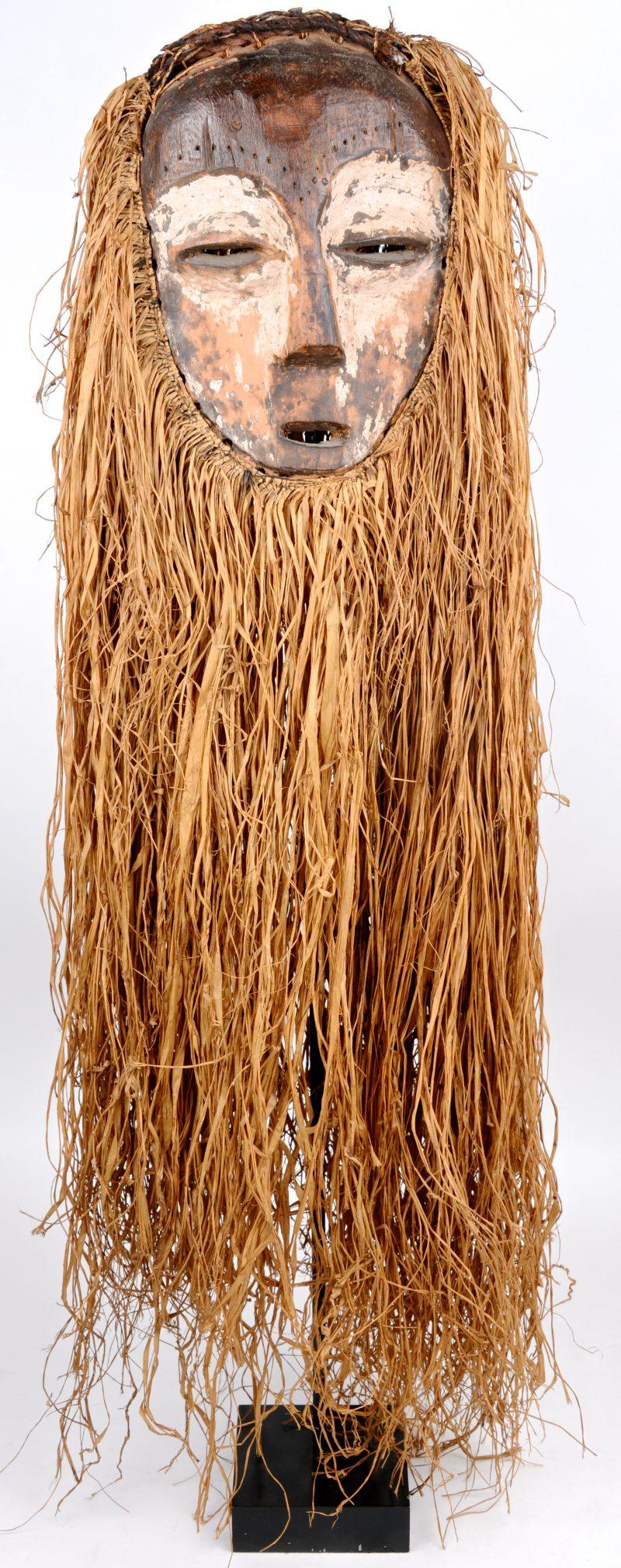 Een Afrikaans masker van hout en stro. Op metalen staander.