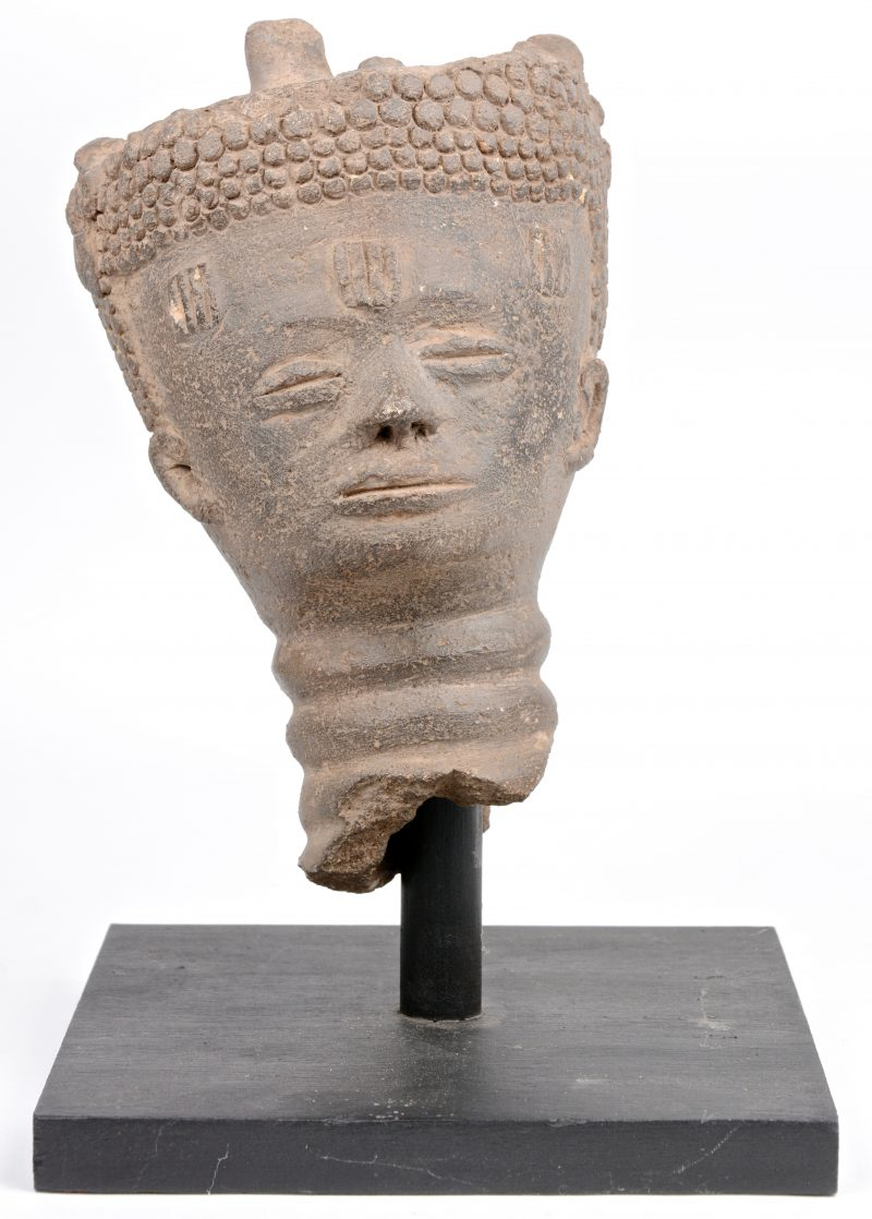 Een Afrikaans aardewerken hoofd op staander.
