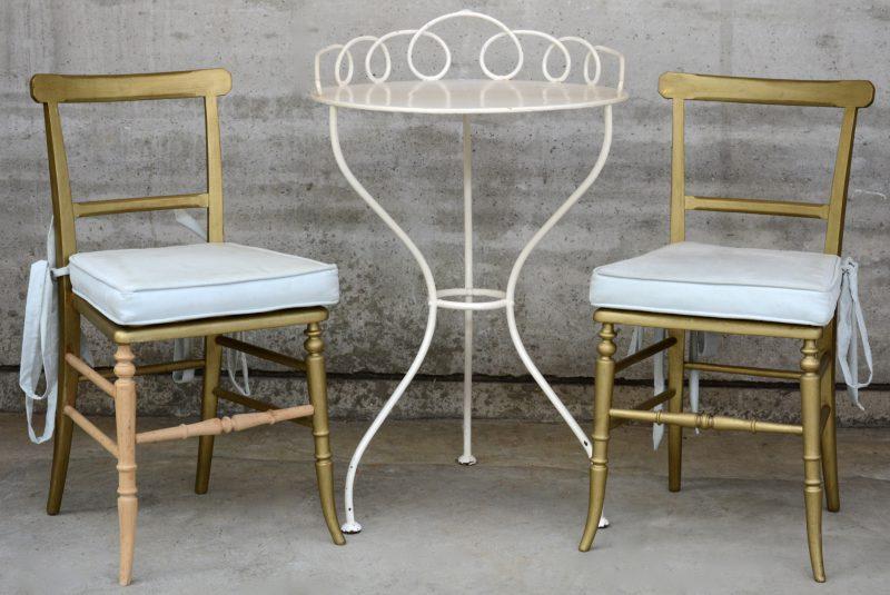 Een witgelakt rond ijzeren tafeltje. Bijgevoegd twee goudgepatineerde stoeltjes.