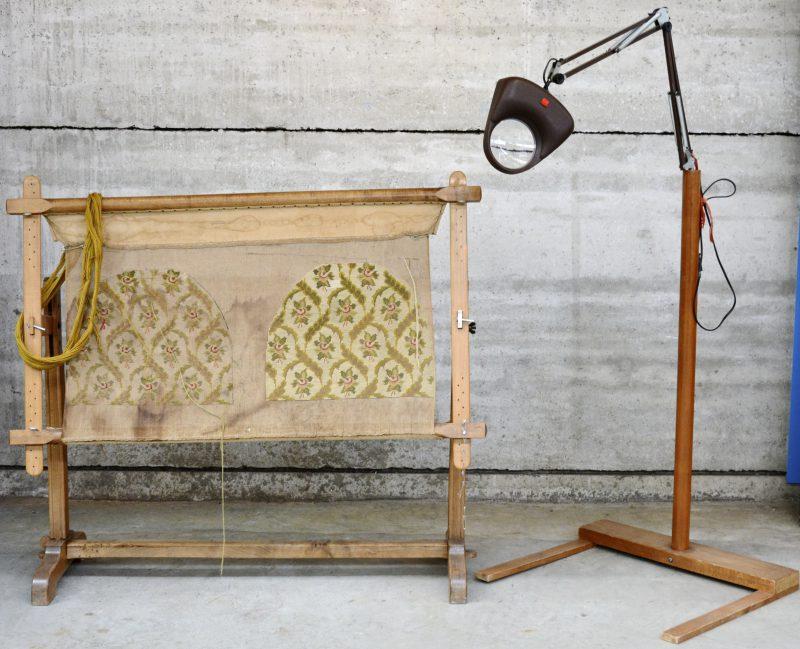 Een houten weefgetouw en een verstelbare lamp met vergrootglas.