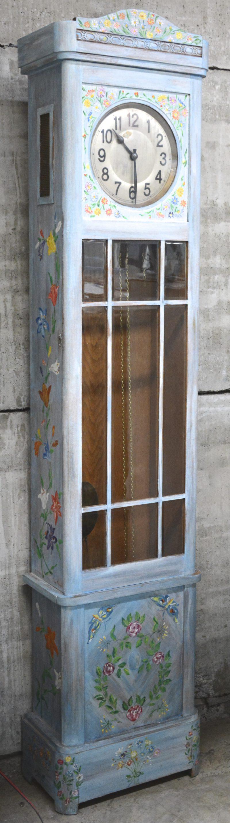 Een staande klok met blauwgepatineerde houten kast en versierd met bloemen en vlinders.