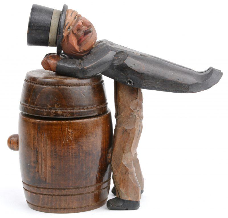 Een sigarettendoos van gebeeldhouwd en gepolychromeerd hout in de vorm van een man met hoge hoed op een ton.