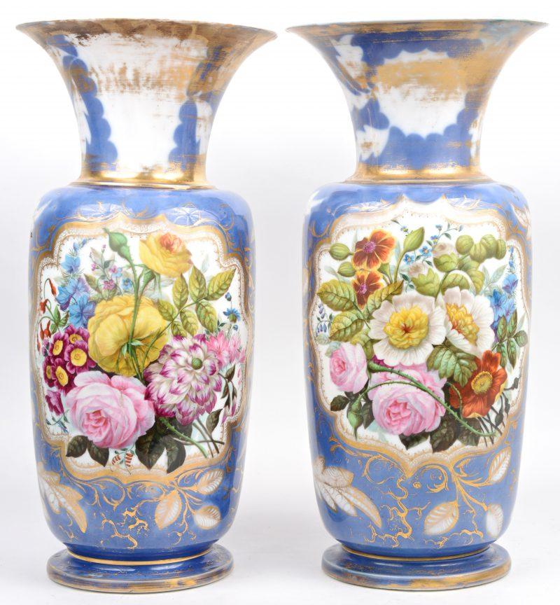 Een paar Frans porseleinen vazen met een handgeschilderd meerkleurig bloemendecor in gouden omlijsting op blauwe fond. Lichte randschade aan de voet.