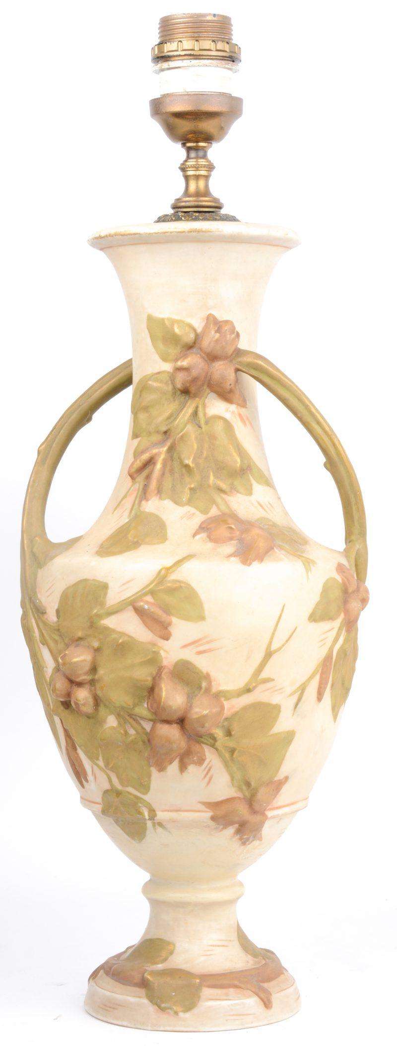 Een siervaas van meerkleurig porselein, versierd met een decor van noten en bladeren in reliëf. Gemonteerd als lampvoet.
