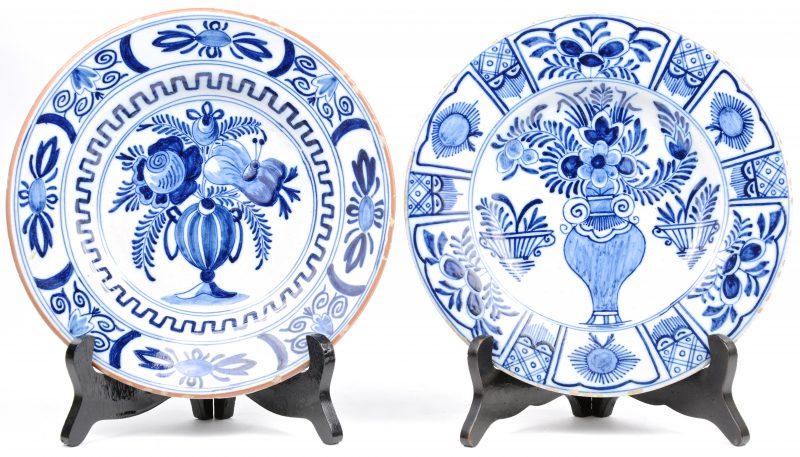 Twee borden van blauw en wit Delfts aardewerk , versierd met bloemenvazen op he plat. Kleine randschade. XIXe eeuw.