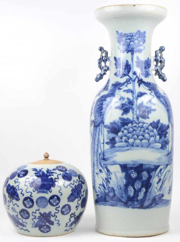 Een Chinese vaas en gemberpot met blauwe versieringen. Op de vaas twee pauwen in een tuin en op de gemberpot florale motieven. Kleine barst in de basis