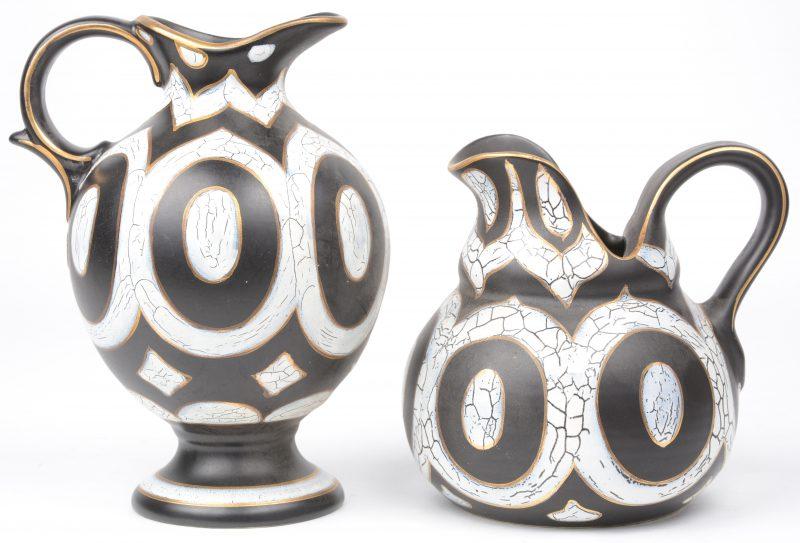 Een bol kruikje en een kannetje van zwart plateel met wit en verguld decor 'Cameo'. Onderaan gemerkt. Gaaf.