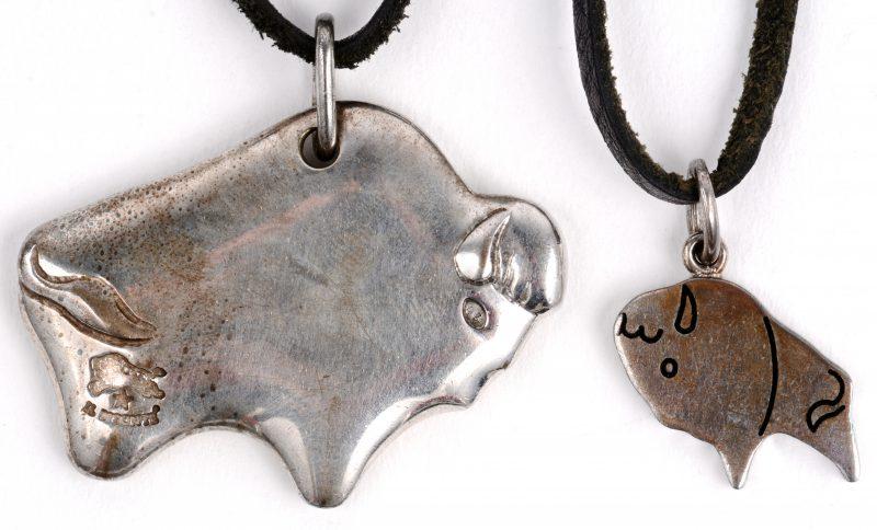 Twee verschillende zilveren hangers met lederen koord. In originele doos en hoesje.