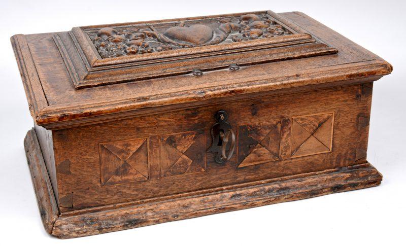 Een antiek eikenhouten koffertje, versierd met ingelegde motieven op de zijkanten en het deksel versierd met een gbeeldhouwde voorstelling van het Heilig Hart.