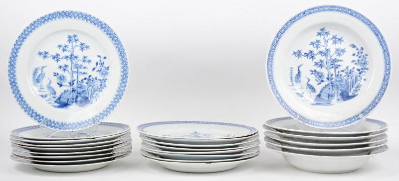 Een reeks van zes diepe en zestien platte borden van Chinees porselein met blauw op witte decors van reigers in een landschap. Tijdperk Qianlong. Diverse schilfers en haarscheuren.