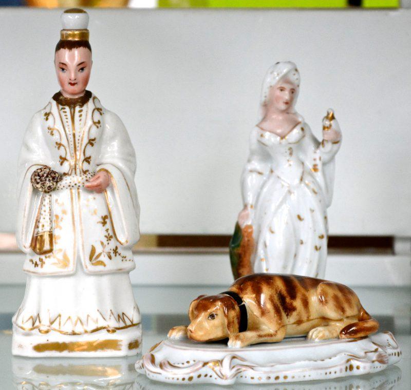 Een lot meerkleurig en verguld Brussels porselein, bestaande uit twee flesjes, waarbij in de vorm van een man, het ander in de vorm van een vrouw met een duif en een liggende hond. Het flesje en de hond met restauraties. XIXe eeuw.