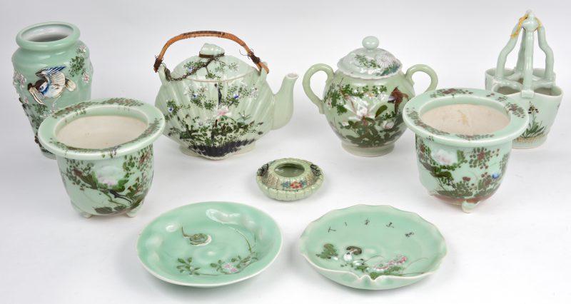 Een lot celadonkleurig porselein, bestaande uit twee kleine jardinières met verschillende onderschalen, een vaas, een bloemenemmerjte, een suikerpotn een theepot en een inktpot. De theepot met haarscheuren.