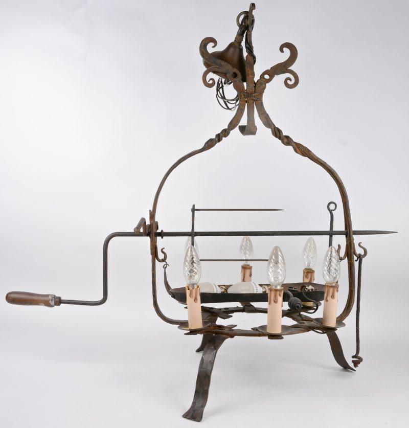 Een oud smeedijzeren draaispit, gemonteerd als luchter.