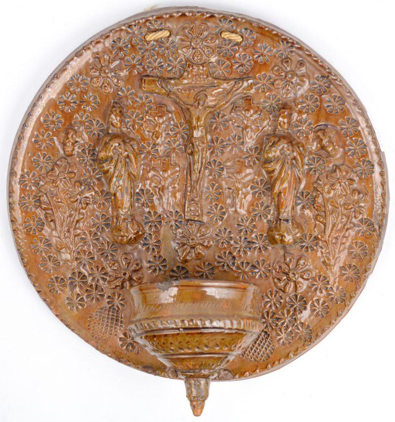 Een wijwatervat van geglazuurd terracotta met reliëfdecor. Schilfer.