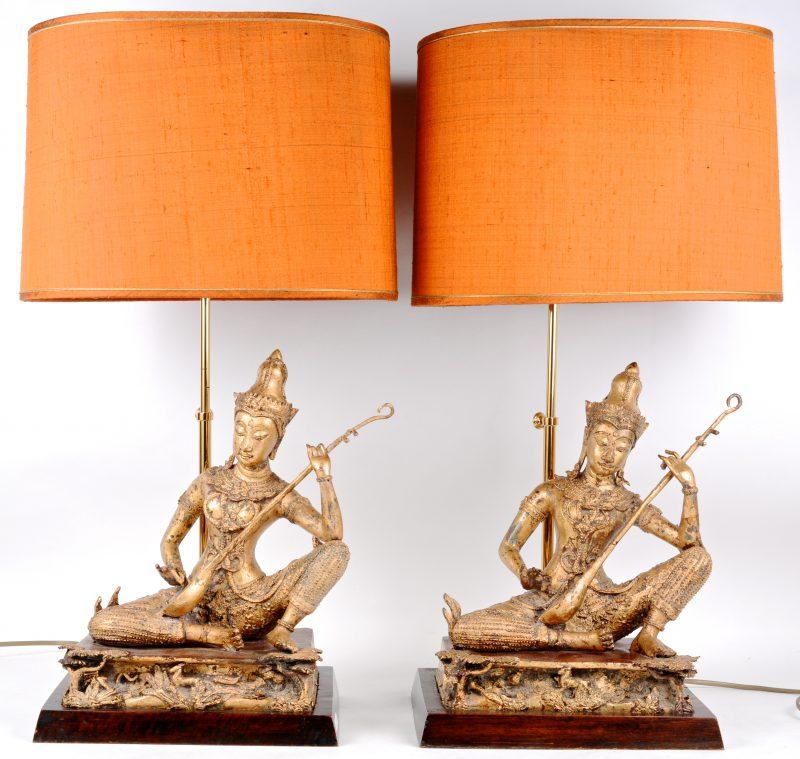 Een paar lampvoeten van verguld brons in de vorm van musicerende tempelwachters.