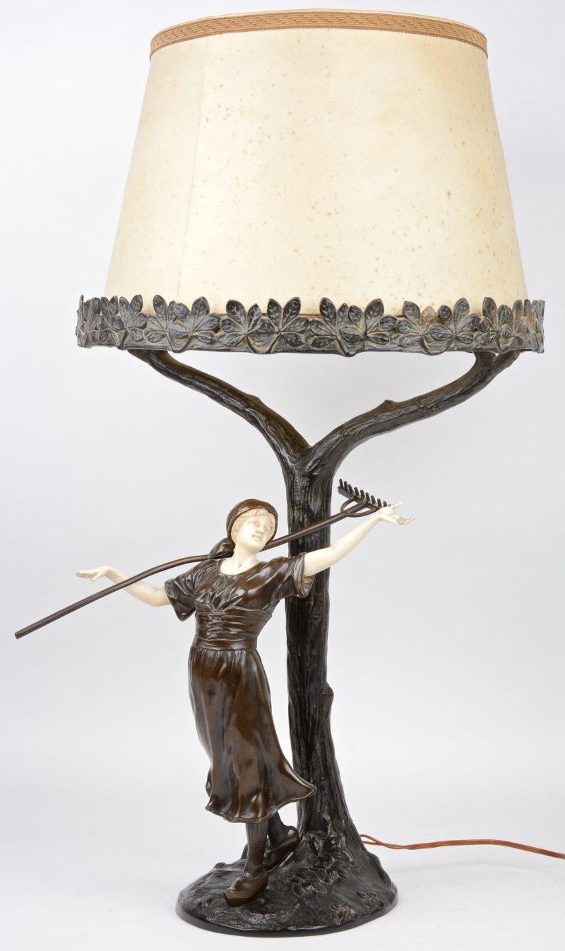 Een bronzen schemerlamp in de vorm van een boerin onder een boom. Ivoren (?) handjes en hoofdje. Enkele vingertjes afgebroken. Zonder originele kap.