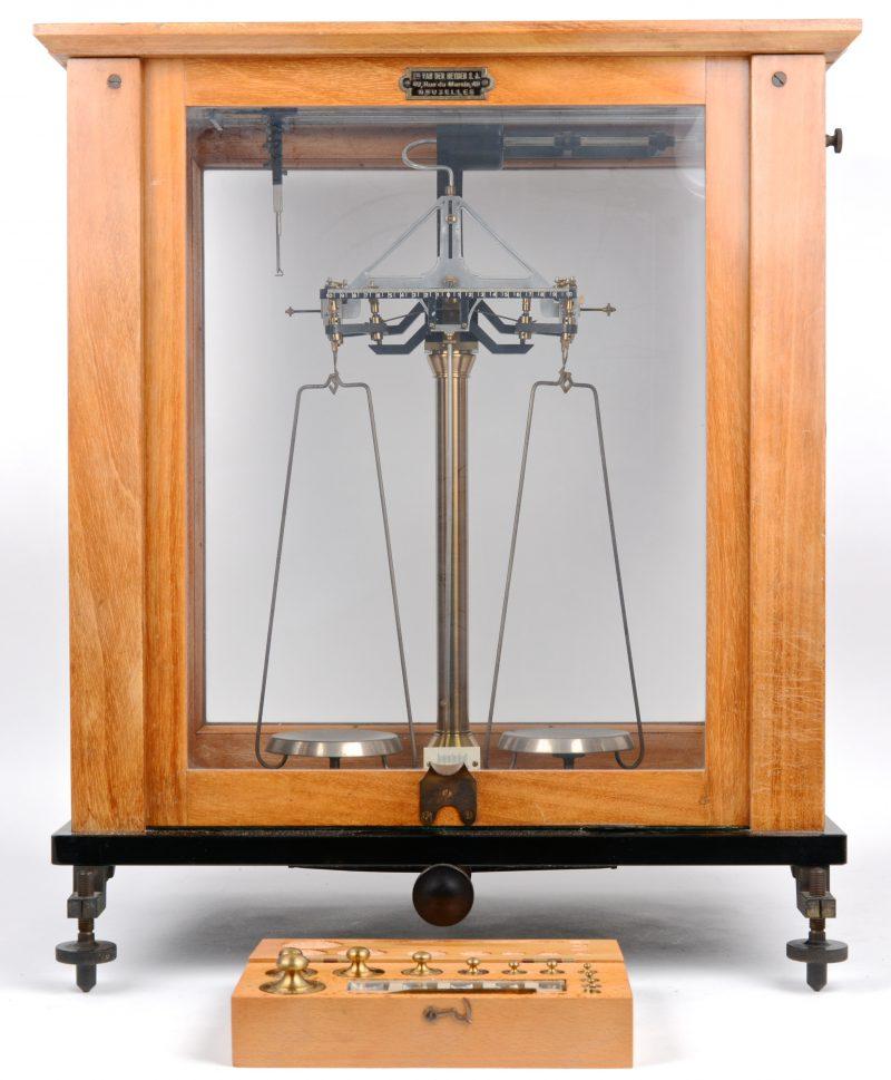 Een apothekersweegschaal in vitrine. Bijgevoegd een complete gewichtenset.