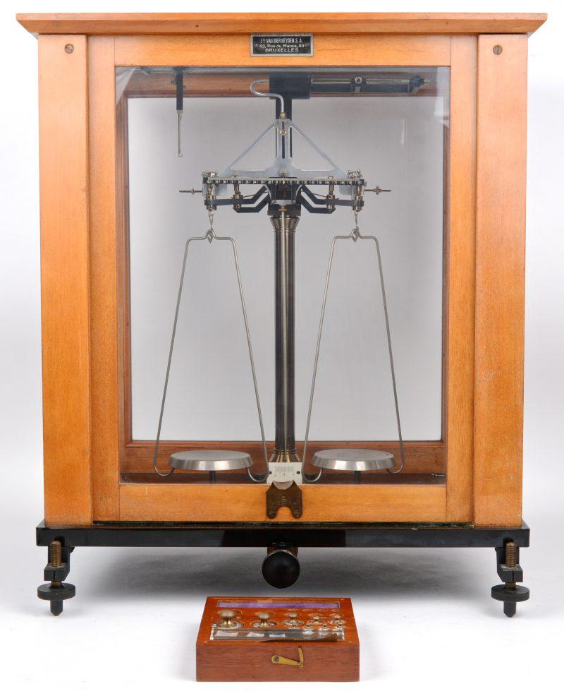 Een apothekersweegschaal in vitrine. Bijgevoegd een volledig gewichtensetje.