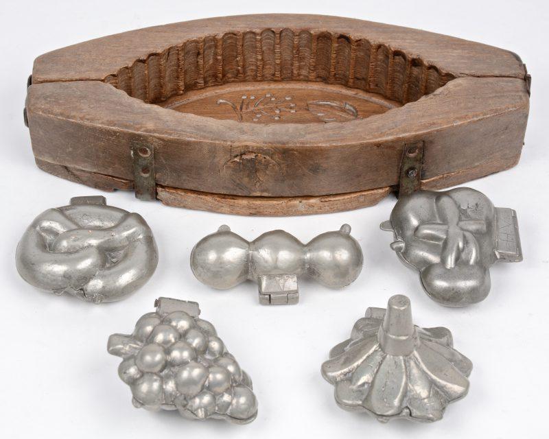 Een lot van vijf oude tinnen chocoladevormen en een grote houten vorm.