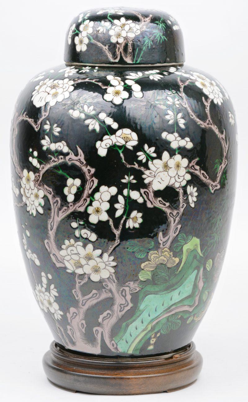 Een dekselvaas van Chinees porselein met een meerkleurig decor van bloesems op zwarte fond.