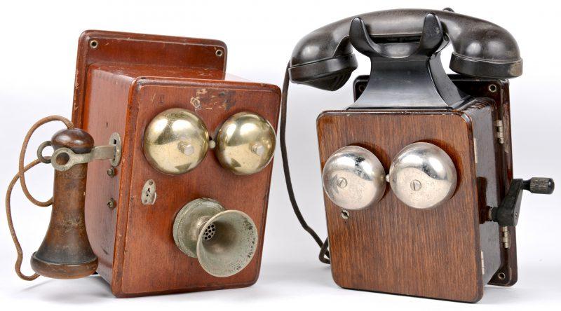 Twee oude houten wandtelefoons met bakelieten hoorn. Een gedateerd 1947 binnenin. Eén sleuteltje manco.
