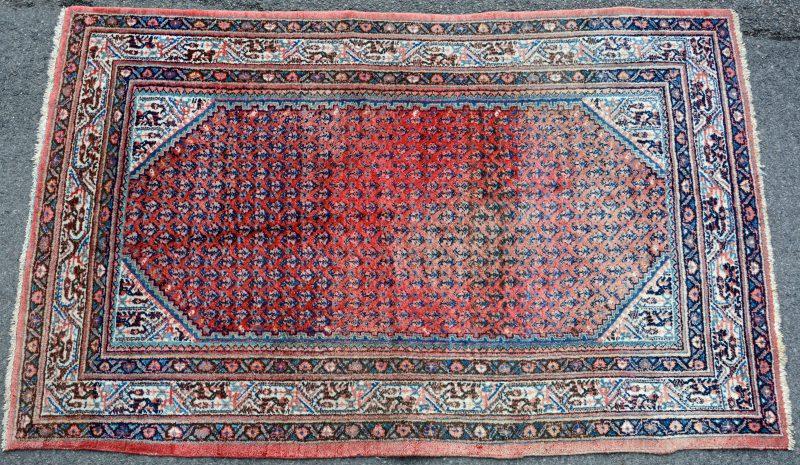 Een handgeknoopt Oosters wollen karpet. Lichte verkleuring.
