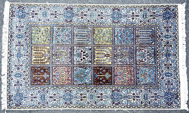 Een handgeknoopt zijden kleed met diverse bloemendecors in achttien vlakken.