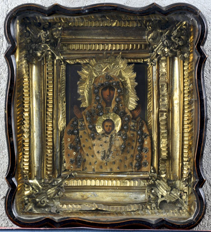 """""""Moeder Gods met Christus"""". Een Oekraïnsche icoon met fraai uitgewerkte messingen riza. Achter glas. XIXe eeuw."""