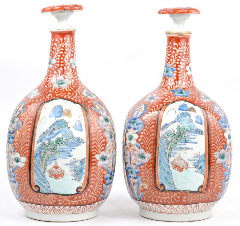 Een paar flesvazen van Chinees porselein met een decor van vogels, bloesems en landschappen in cartouches op een rode fond, versierd met bloemen. Stoppen intact. Onderaan gemerkt.