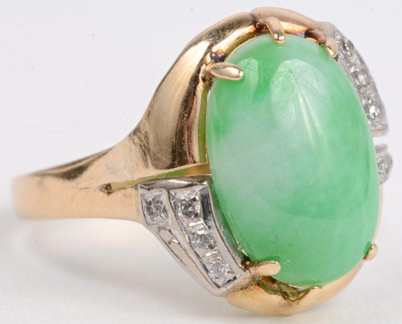 Een 18 karaats wit en geel gouden ring bezet met diamanten oude slijp met een gezamenlijk gewicht van ± 0,20 ct. en een ovale jade cabochon van ± 5 ct.