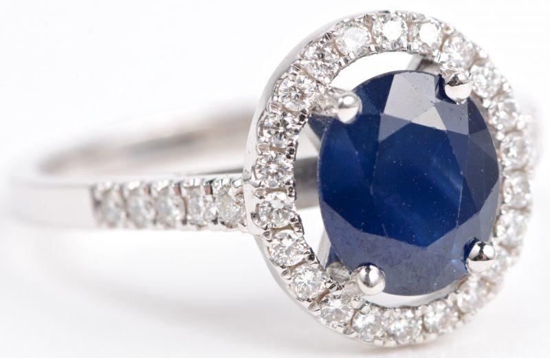 Een 18 karaats wit gouden ring bezet met diamanten met een gezamenlijk gewicht van ± 0,34 ct. en een ovale saffier van ± 1,16 ct.