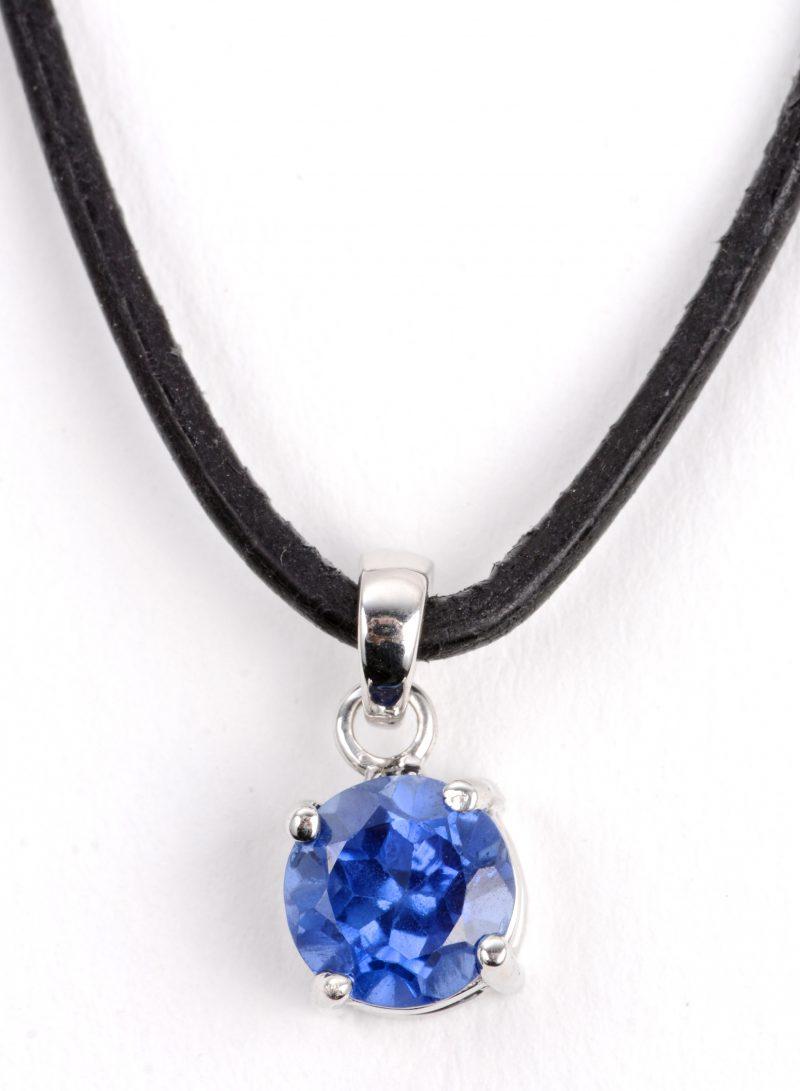 Een 18 karaats wit gouden hanger bezet met een blauwe amethist van ± 1,31 ct. en met zwart lederen ketting.