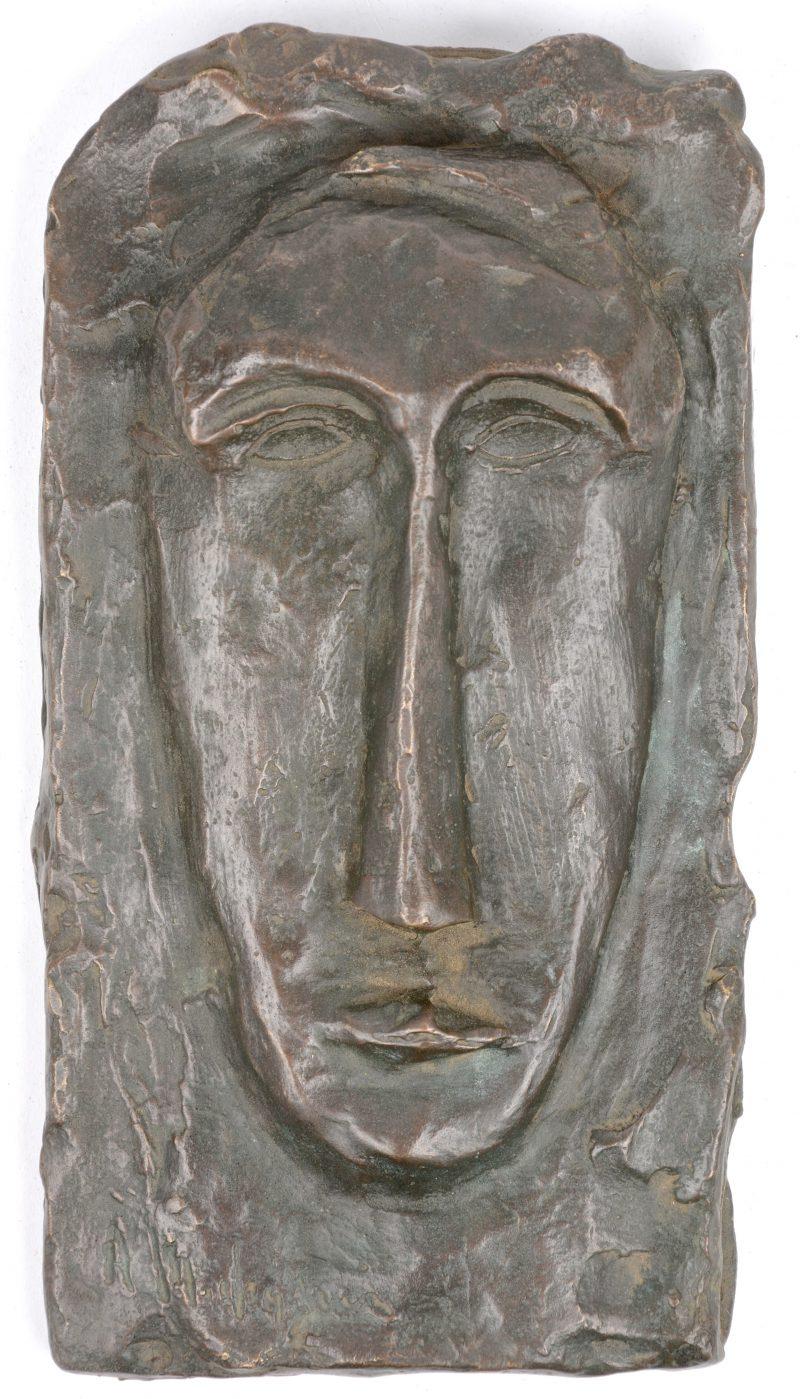 Een bronzen gestileerd hoofd in hoogreliëf naar een werk van Modigliani.