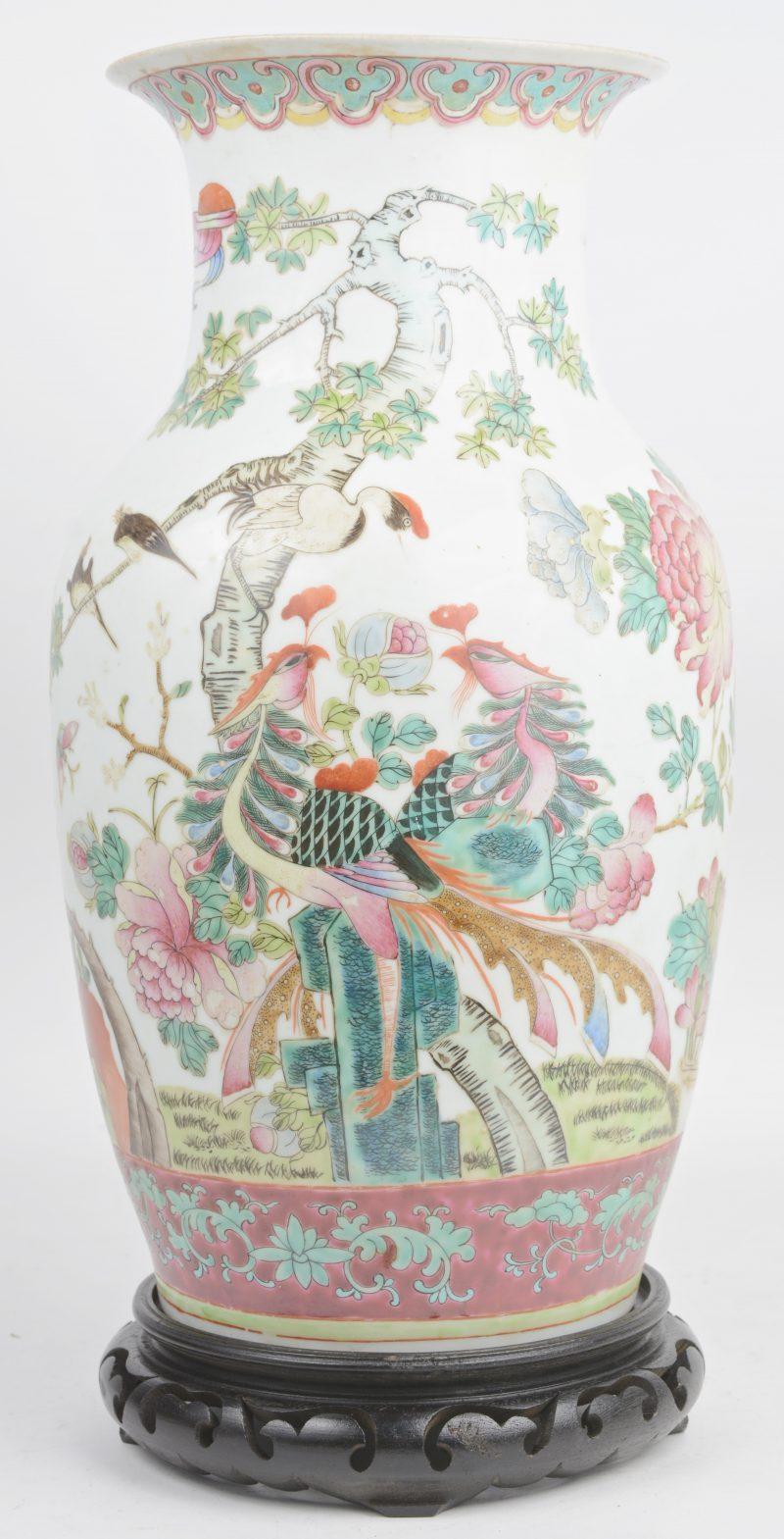 Chinese vaas van polychroom porselein met een famille rose decor. XXste eeuw. Op houten sokkel.