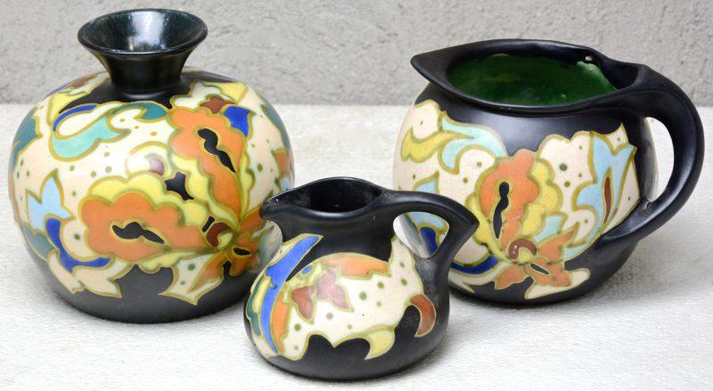 Een lot meerkleurig aardewerk, bestaande uit een bolle vaas en twee verschillende kannen. Onderaan gemerkt.