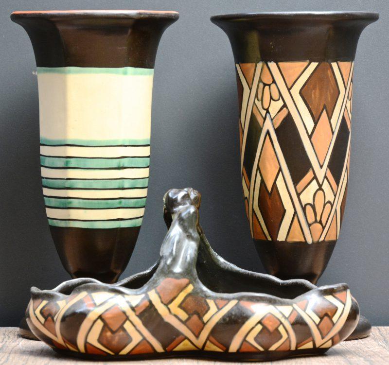 Twee vazen op voet en een mandje van meerkleurig aardewerk. Tijdperk art deco. Onderaan gemerkt.