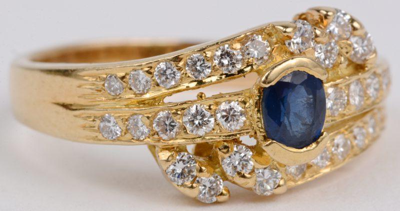 Een 18 karaats geel gouden ring bezet met diamanten met een gezamenlijk gewicht van ± 0,35 ct. een centrale saffier van ± 0,20 ct.