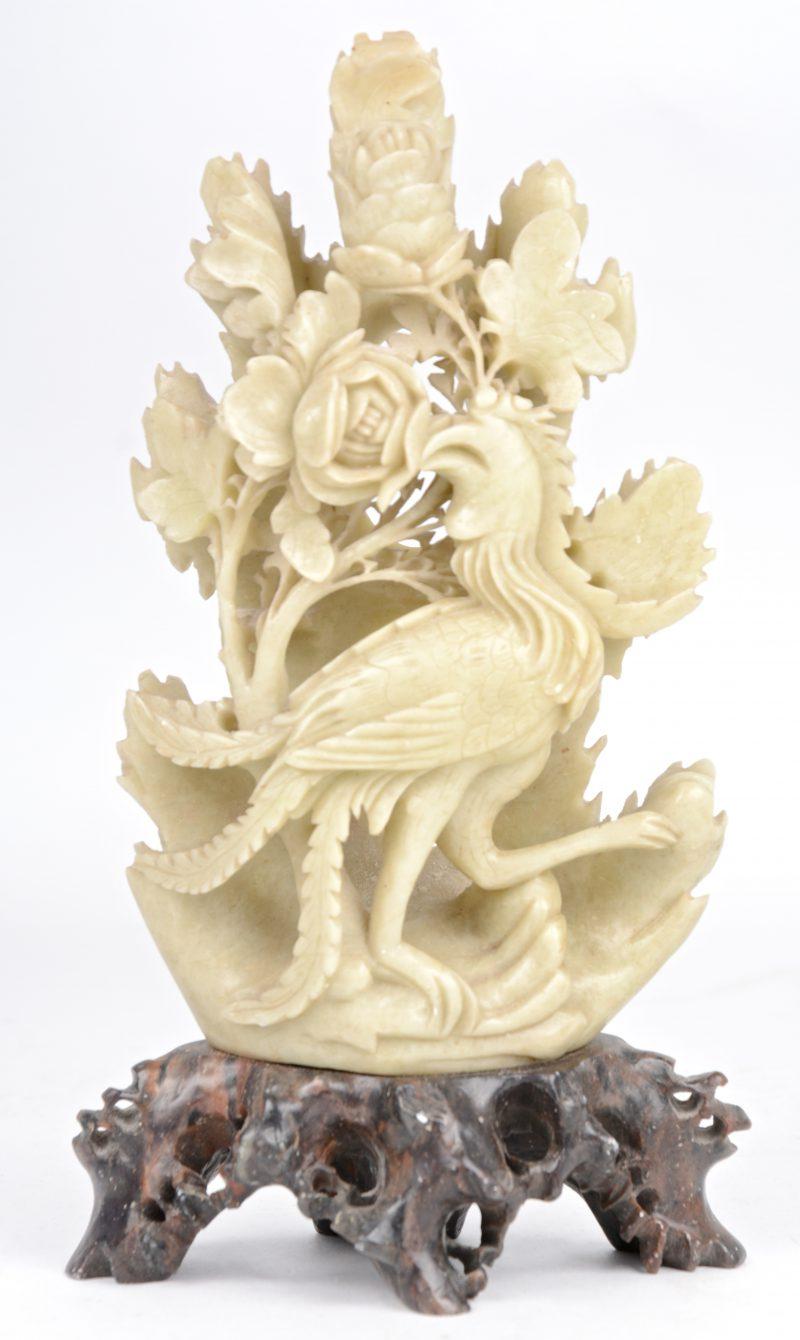 Een gebeeldhouwd jaden grope in de vorm van een vogel en pioenen.