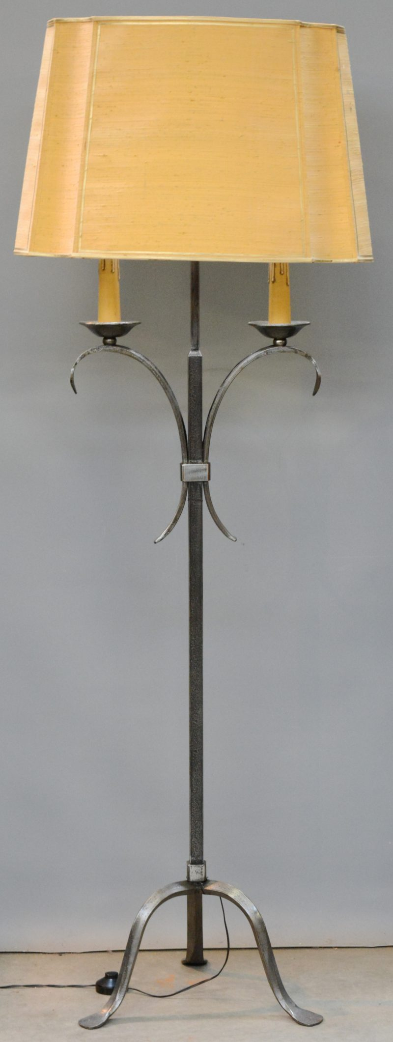 Een smeedijzeren dubbele kandelaar, gemonteerd als staande lamp.