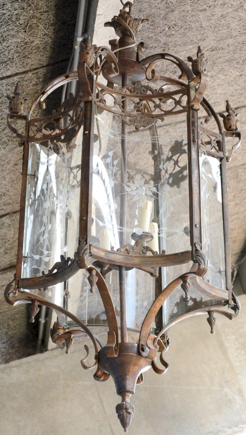 Een grote bronzen hall-lantaarn met bol gegraveerd glas.