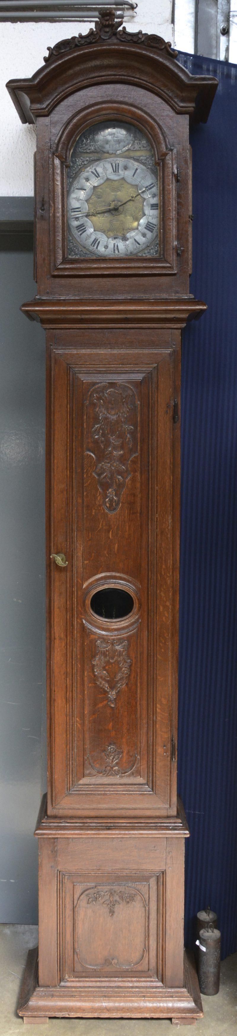 Een staande klok met gebeeldhouwd eikenhouten kast, versierd met motieven in Lodewijk XVI-stijl. Het werk gesigneerd en gedateerd 1793.