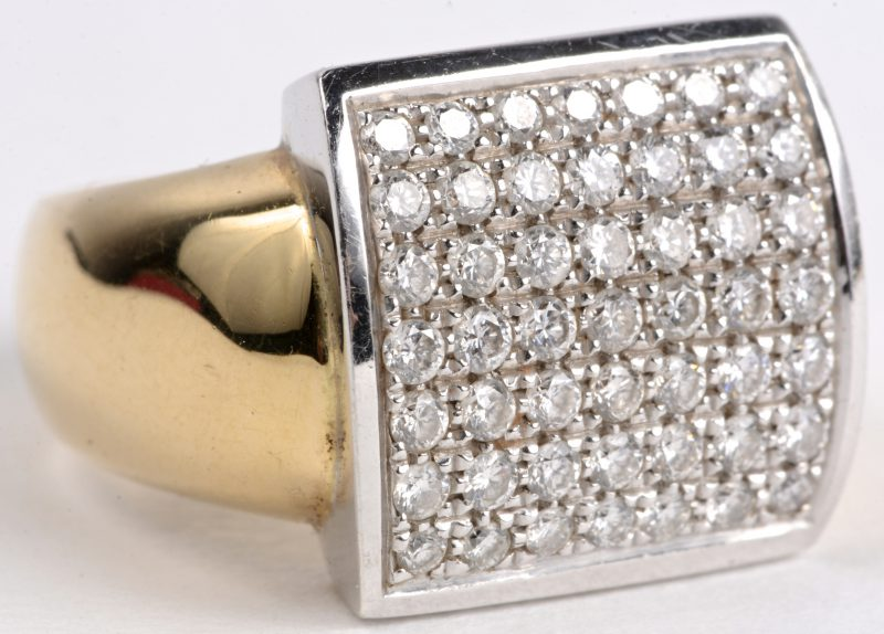 Een 18 karaats wit en geel gouden ring bezet met diamanten met een gezamenlijk gewicht van ± 0,90 ct.
