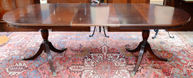 Een tafel in Regencystijl op twee voeten, telkens eindigend in drie bronzen leeuwenpoten. Met verlengblad.