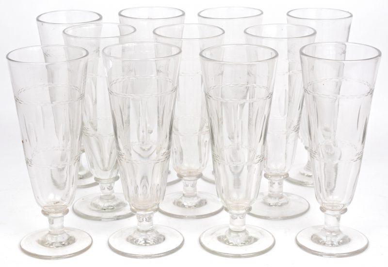 Een lot van elf kleurloos glazen vazen op voet.