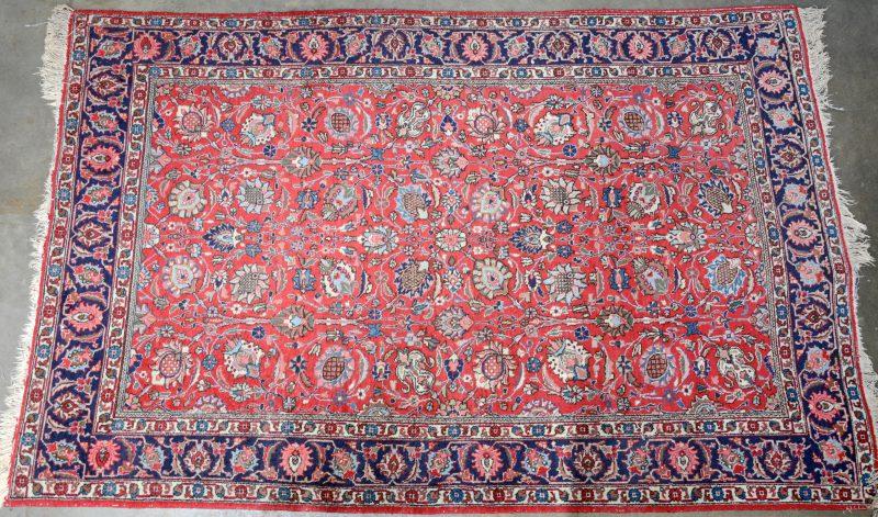 Handgeknoopt wollen tapijt. Centraal bloemenmotief op rode fond. Brede boord met herati op nachtblauwe fond. Slijtage.