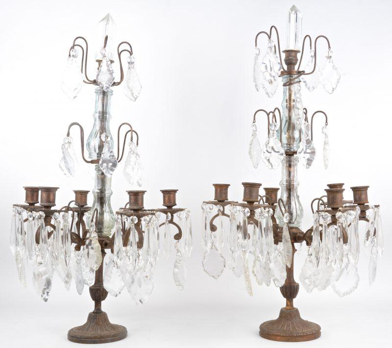Een paar bronzen girandoles met zes lichtarmen, versierd met kristallen pendeloques.