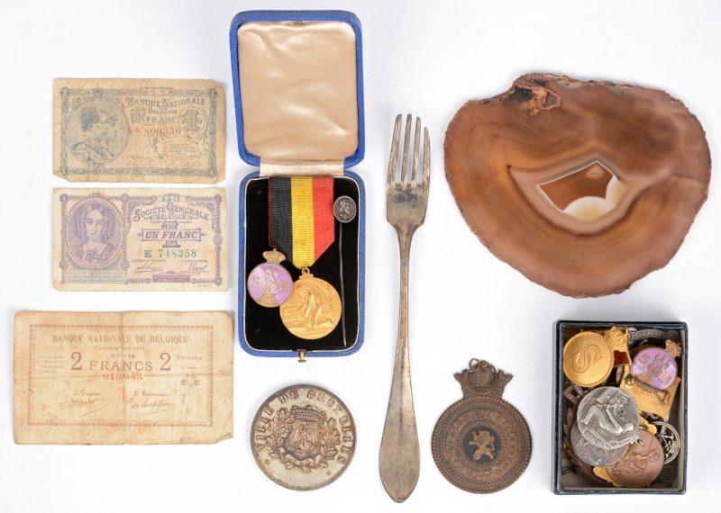 Een lot medailles en speldjes (een dertigtal). Overwegend m.b.t. W.O. I en Albert I. Evenals drie biljetten (van 1 en van 2 BEF) van 1914, '15 en '20, een gepolijste schijf van een geode en een oude zilveren vork. Delheid 1815-1832.