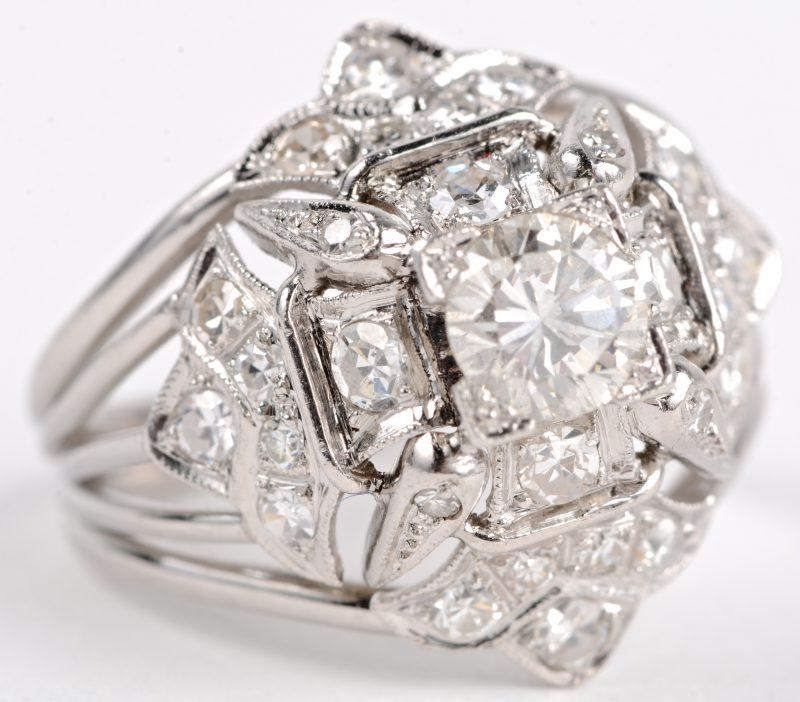 Een 18 karaats wit gouden ring bezet met een centrale diamant van ± 0,50 ct. en diamanten met een gezamenlijk gewicht van ± 0,80 ct. VS2.