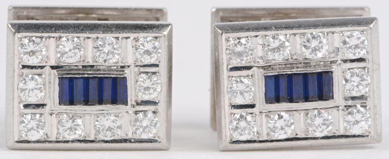 Een paar 18 karaats wit gouden manchetknopen bezet met diamanten en baguetten met een gezamenlijk gewicht van ± 4,50 ct. SI. en saffier baguetten met een gezamenlijk gewicht van ± 0,50 ct.